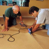 two men and women utilizing an electric seaming metal to show how-to install carpet